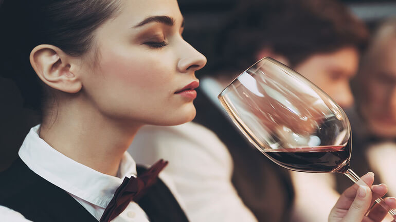 sommelier in divise che assaggiano vino